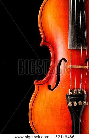 Old violin on a black background. A musical stringed instrument for musical performance