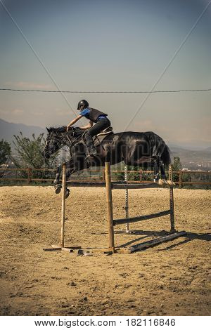 Equestrian sports Black horse approaching. Jockey riding a fast thoroughbred horse