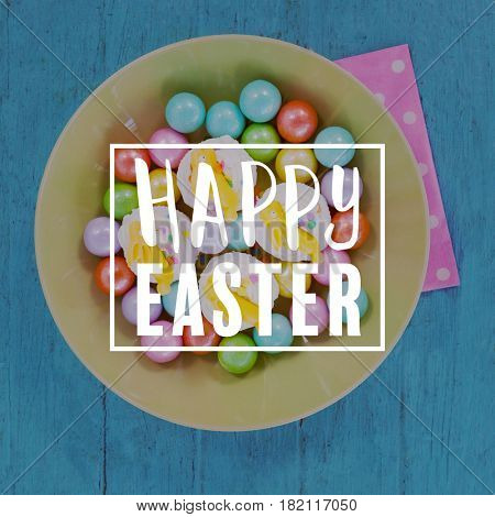 Easter greeting against colorful chocolates and cupcakes in bowl
