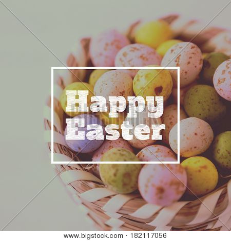 happy easter against colorful easter eggs in wicker basket