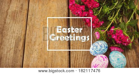 Easter greeting against painted easter eggs and pink flower on wooden table