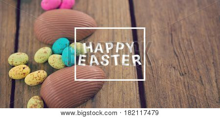 Easter greeting against chocolate easter eggs on wooden plank