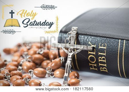 Easter message against black leather bound holy bible with rosary beads