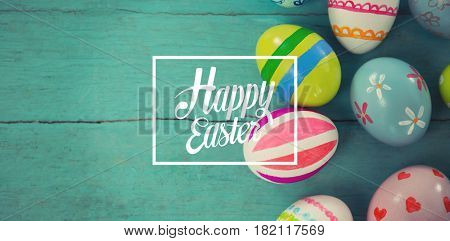 Happy easter against painted easter eggs on wooden plank