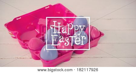 Happy easter against pink and purple easter eggs in carton