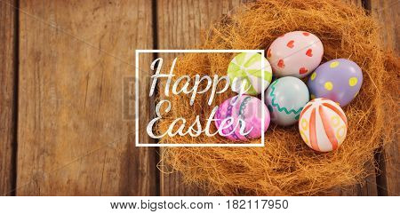 happy easter against painted easter eggs in nest