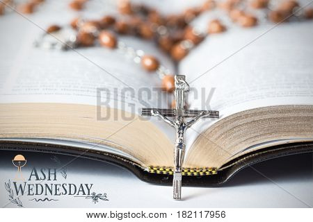 Easter message against cross of rosary beads resting against bible