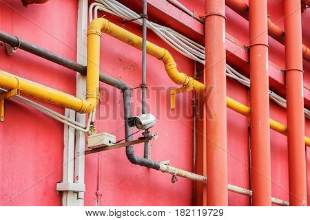 View Of Pipe System Outside A Red Building