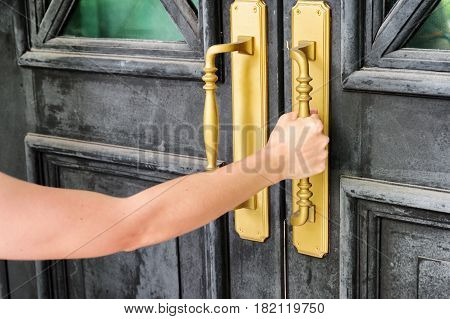 Female hand holding golden main door handle. Opening a black old vintage door.