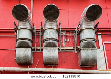 Ventilation Pipes Outside A Red Building. Industrial Concept