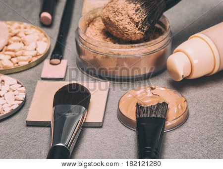 Makeup products to even skin tone and complexion. Foundation, concealer, powder with make up brushes. Retro style processing