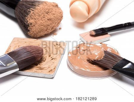Basic makeup products to create beautiful skin tone and complexion. Corrector, foundation, powder with brushes on white background. Shallow depth of field