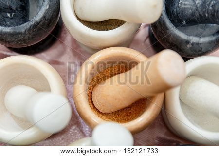Many mortar and pestle different colors with seasoning