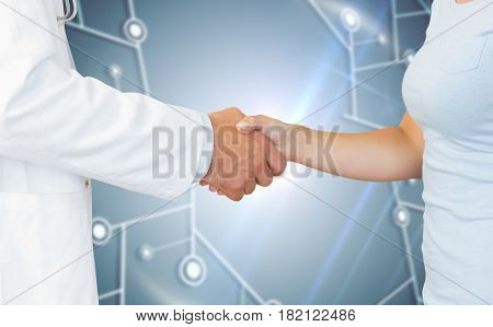 Doctor and patient shaking hands against black background with glowing network