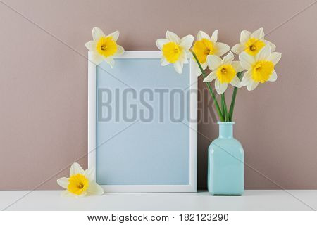 Mockup of picture frame decorated narcissus flowers in vase with clean space for text your blogging and greeting for mother day.