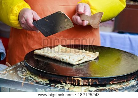 Close up of making crepe with jam outdoors on skillet