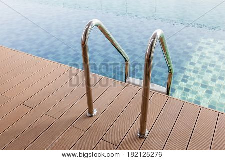 Grab bars ladder entrance to the clear blue swimming pool.