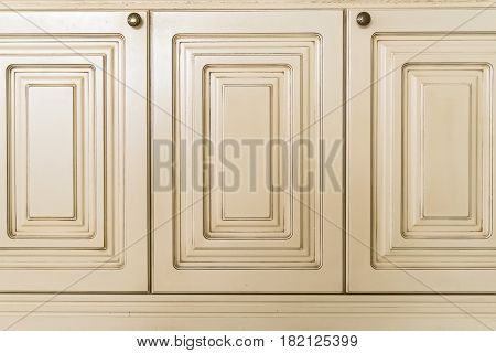 Close up of three white wooden doors of cupboard with metal knobs