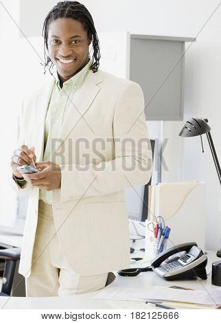 African businessman holding electronic organizer