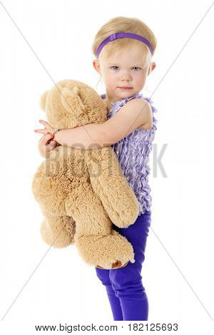 An adorable 2-year-old looking at the viewer as she hugs her big, fluffy Teddy bear.  On a white background.