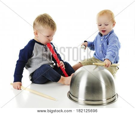 Two toddlers making music together on recorders and an upside down metal bowl.  On a white background.