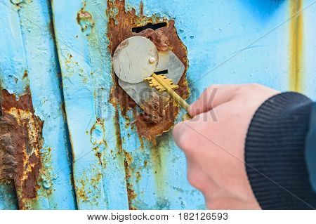 Close-up photo of hands opening obsolete metal door with key