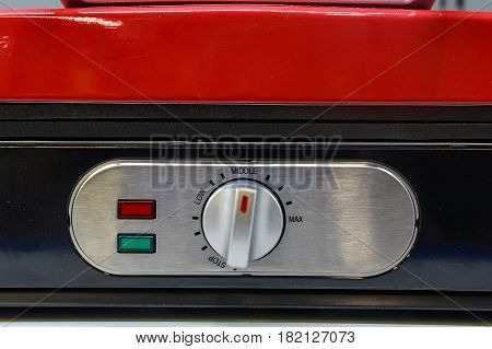 Closeup red electronic device with rheostat regulator knob and red and green light