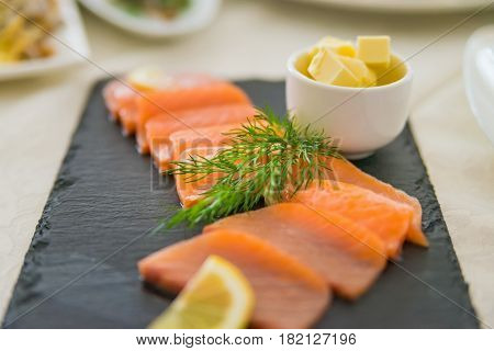 Closeup slices of red fish served with dill and butter in restaurant