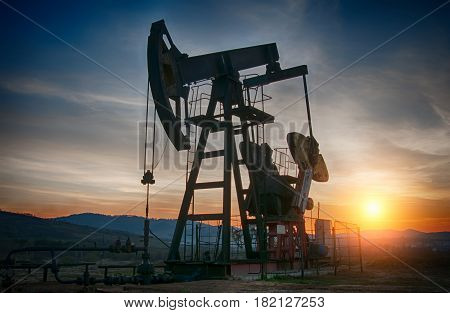 oil pump on orange sunset. A close up