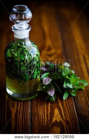 Mint syrup in a glass bottle on a wooden table