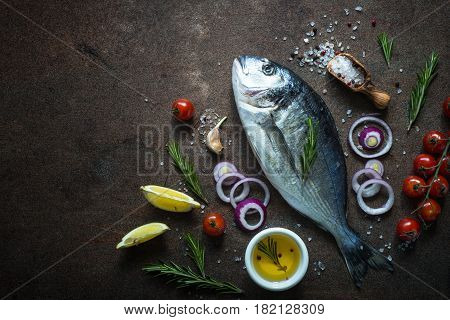 Fresh fish dorado. Dorado and ingredients for cooking at dark rusty table. Top view copy space.
