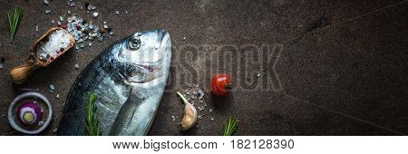 Fresh fish dorado. Dorado and ingredients for cooking at dark rusty table. Top view with copy space. Long banner format.