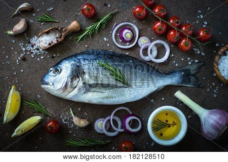 Fresh fish dorado. Dorado and ingredients for cooking at dark stone table. Top view.