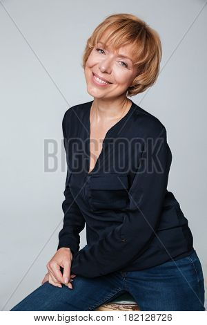 Photo of a happy mature woman sitting and posing isolated over grey wall. Looking at camera.