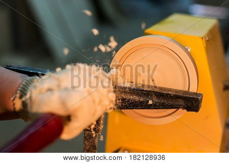 turning a wooden plate on a lathe in a carpenter's workshop