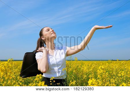 Business woman with briefcase relaxing in flower field outdoor under sun. Young girl in yellow rapeseed field. Beautiful spring landscape, bright sunny day