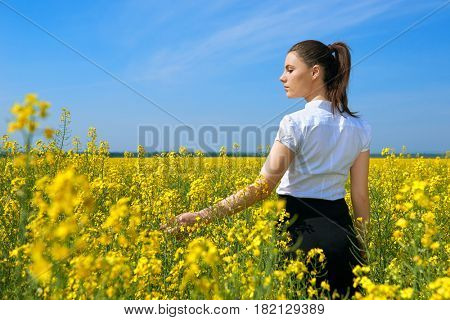 Girl in yellow flower field, beautiful spring landscape, bright sunny day, rapeseed