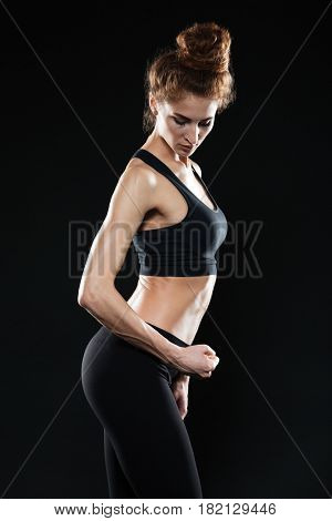 Side view image of young sports lady standing over black background and posing. Looking aside.