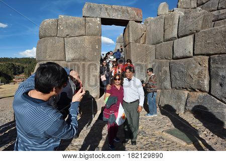 CUSCO PERU - SEPTEMBER 05 2016: Unidentified people posing at Inca wall in the village Saksaywaman on September 05 2016 In Cusco Peru. Saksaywaman is a citadel on the northern outskirts of the city of Cusco.