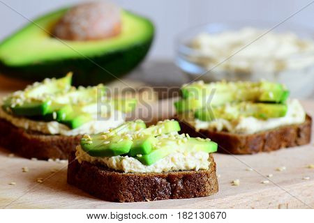 Healthy chickpeas hummus and avocado sandwiches on a wooden board, avocado half, hummus in a glass bowl. Veggie sandwiches made with rye bread, avocado slices, chickpeas hummus and fried sesame seeds