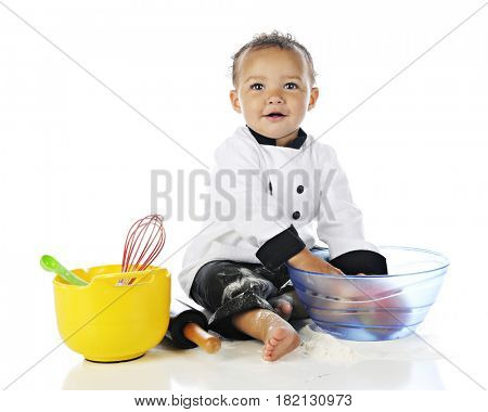 An adorable baby boy wearing a chef's jacket and black pants, playing with apples and cooking utensils, and messed up with white flour.  On a white background.