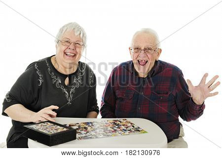 A senior man and woman delighted when they successfully finished their jigsaw puzzle.  On a white background.