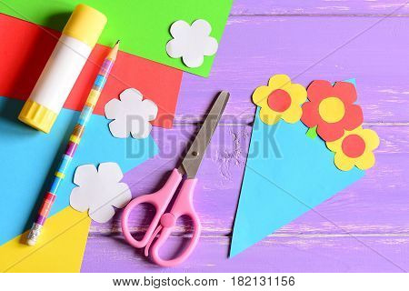 Creating paper crafts for mother's day or birthday. Step. Tutorial. Paper bouquet gift for mommy. Scissors, glue stick, flowers templates, pencil on a table. Easy kids crafts idea. Top view