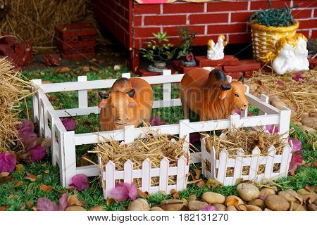 Cows ceramic toy in a farm with seraph cupid background