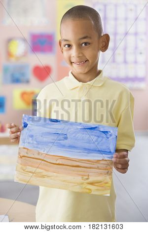 African boy holding painting in classroom