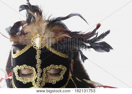 Mixed race woman wearing elaborate mask