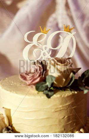 beautiful purple and golden wedding cake with wooden topper