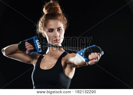 Close-up portrait of a Calm Female fighter using expander over black background