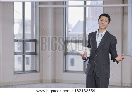 Mixed race man holding blueprints