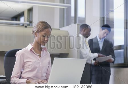 African businesswoman working on laptop in office